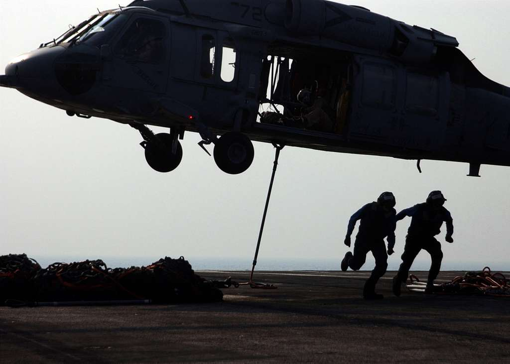 An MH-60S Knighthawk helicopter prepares to lift a bundle of cargo nets from the Nimitz-class aircraft carrier USS Harry S. Truman (CVN 75) during an early morning vertical replenishment.