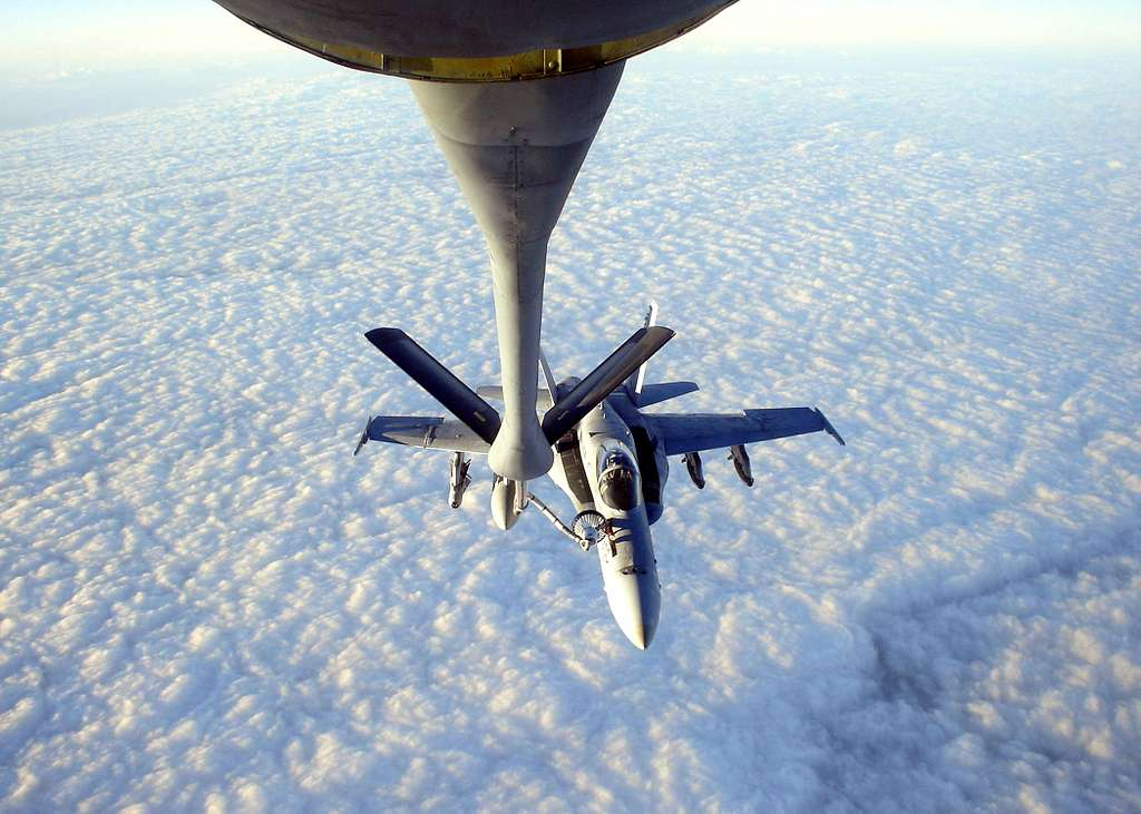 An F/A-18C Hornet assigned to the Gunslingers of Strike Fighter Squadron One Zero Five (VFA-105) receives refuels from an Air Force KC-130.
