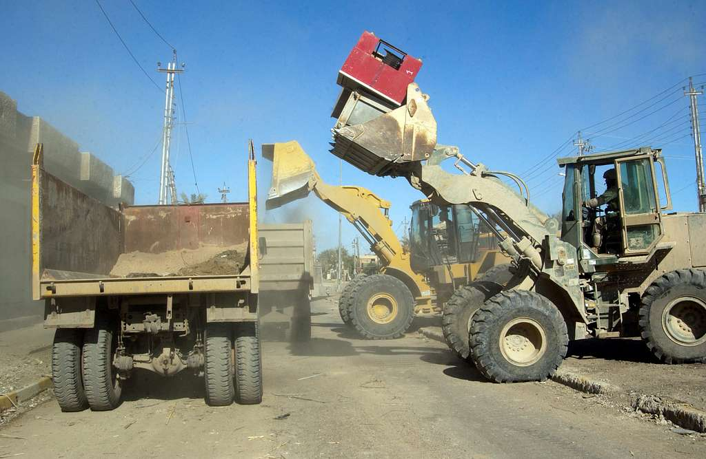 A U.S. Marine Corps front-end loader joins its Army counterpart in filling contracted Iraqi dump trucks with dirt.