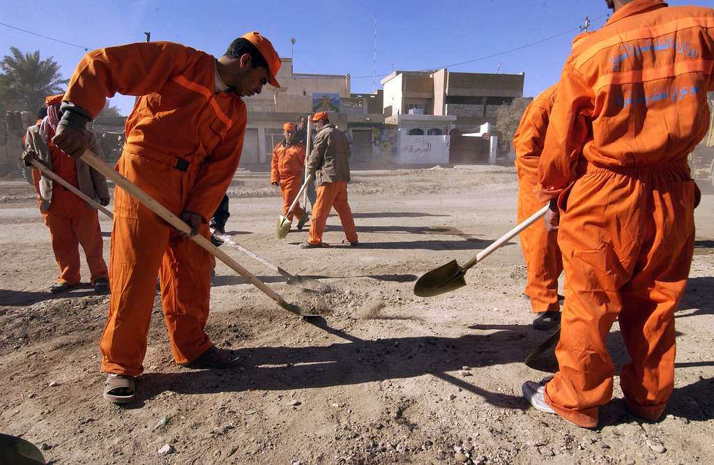 Twenty-two Iraqi contracted nationals, working with brooms and shovels, clear nearly three blocks of broken walls, glass and trash along a major thoroughfare in the city of Fallujah, Iraq.