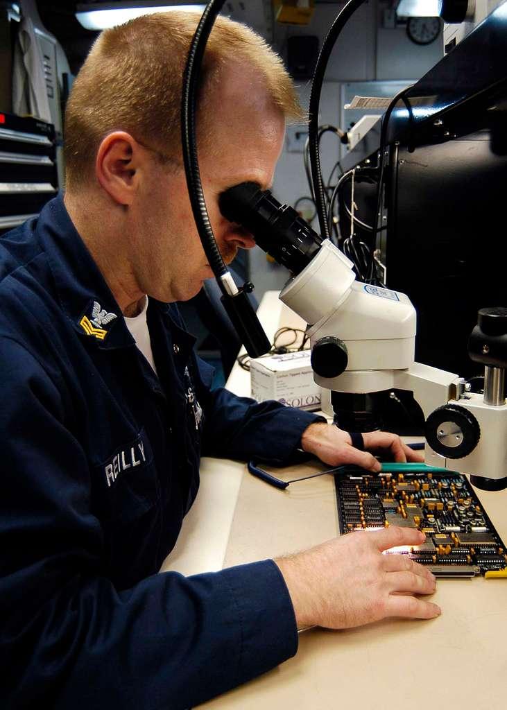 Aviation Electronics Technician 1st Class Jim Reilly inspects a Forward Looking Infrared (FLIR) Servo Control Card.