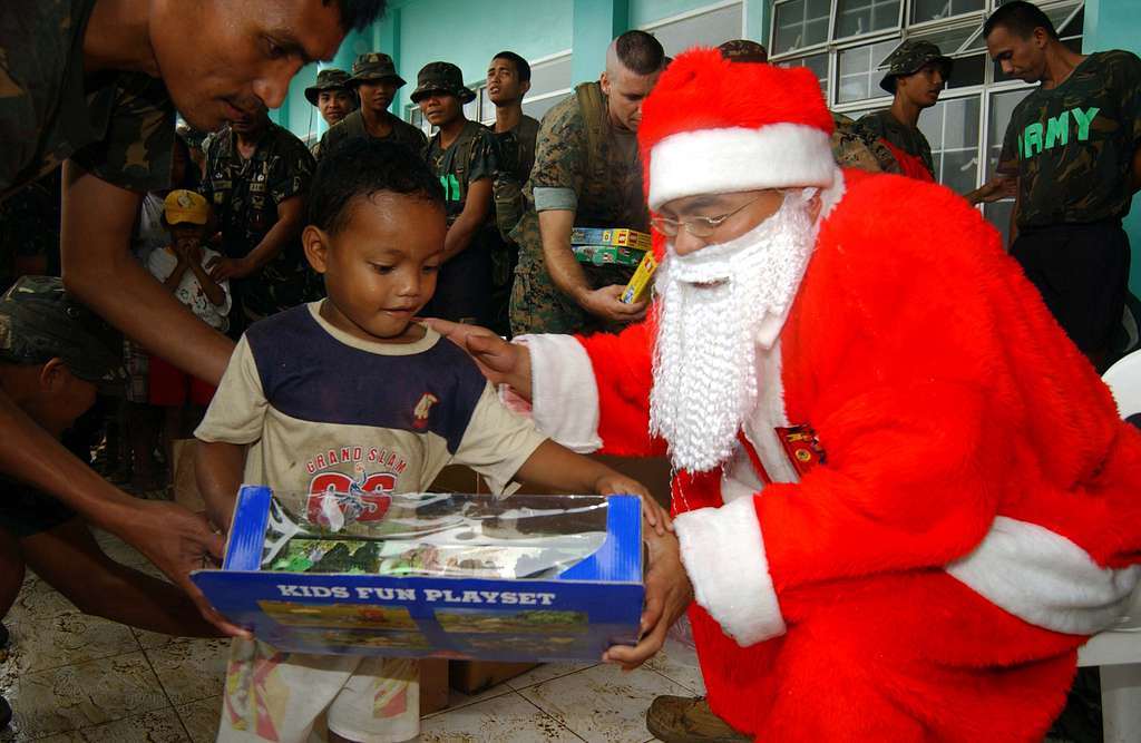 A boy smiles as he receives a gift from Santa Claus during the last day of operations for Joint Task Force Five Three Five (JTF-535) in the Philippines.