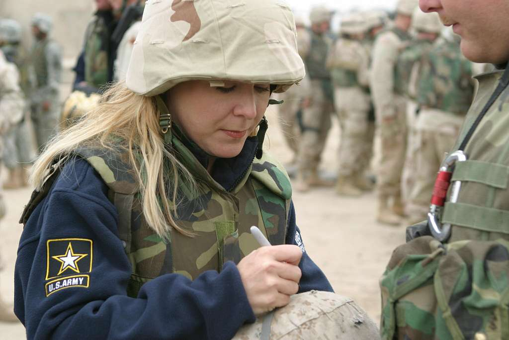 Actress Kerry Turner, autographs the Kevlar helmet for a U.S. Marine assigned to the 1st Battalion 8th Marines, 1st Marine Division, during a USO tour for U.S. troops in Iraq.