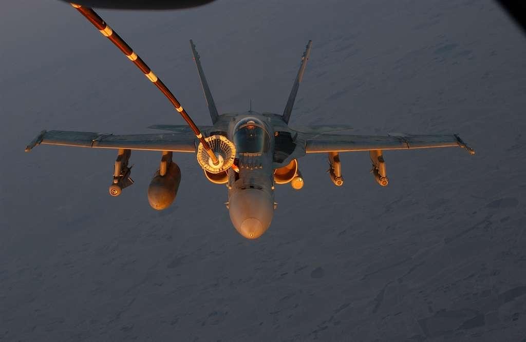 A U.S. Marine Corps F/A-18A+ Hornet receives fuel from a U.S. Air Force KC-10 Extender.