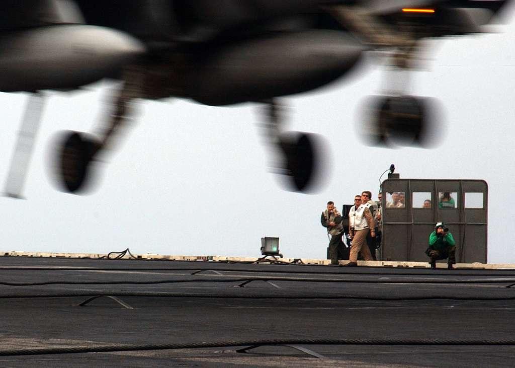 Landing Signal Officers (LSO) grade the arrested landing of an F/A-18 Hornet during flight operations aboard the Nimitz-class aircraft carrier USS Harry S. Truman (CVN 75).