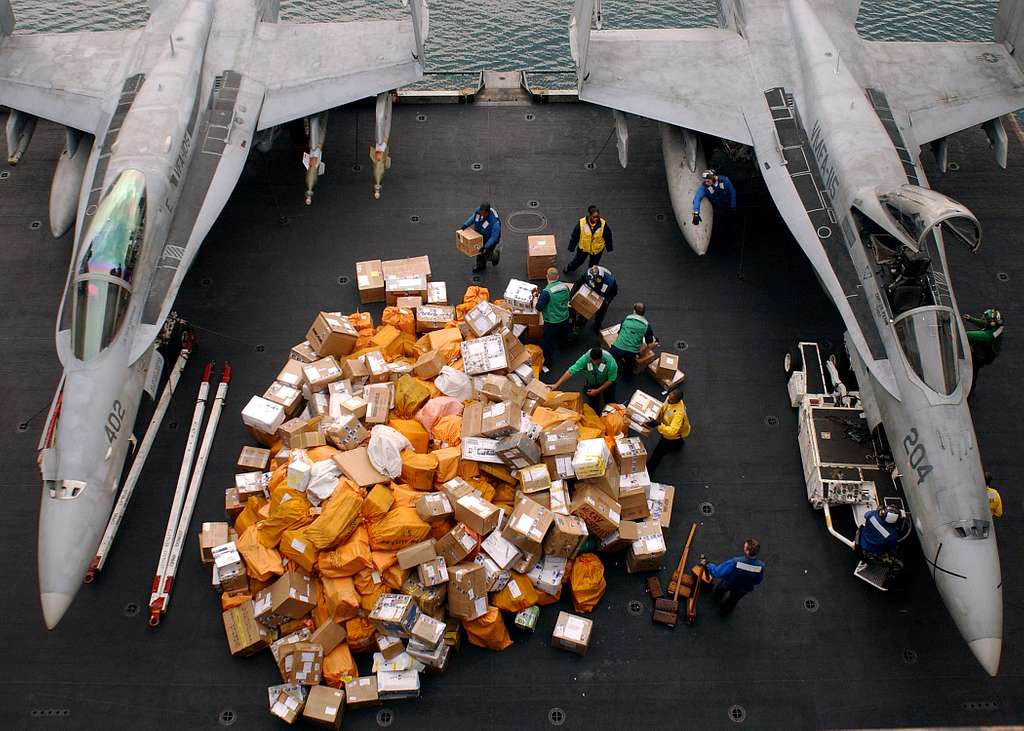 Postal Clerks and bravo working party members begin to move a mountain of packages from one of the aircraft elevators to the hangar bay after receiving the last pre-Christmas mail delivery.