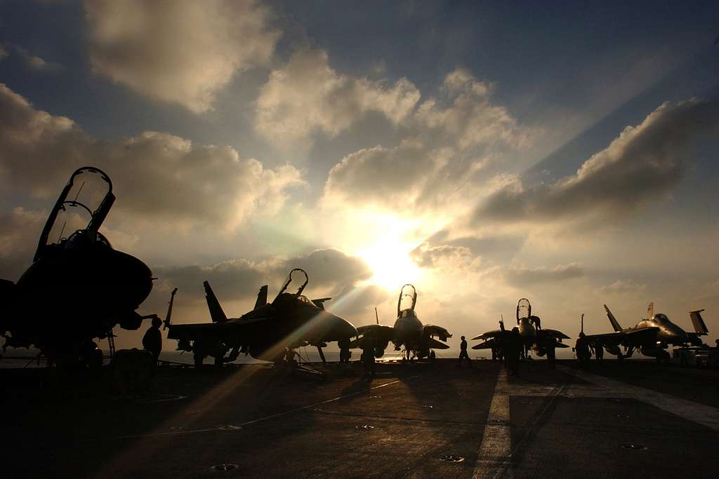 F/A-18 Hornets and F-14B Tomcats sit idle on the flight deck aboard the Nimitz-class aircraft carrier USS Harry S. Truman (CVN 75) after the completion of flight operations.