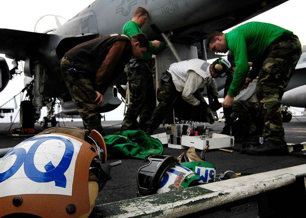 Sailors work on the tail hook of an EA-6B Prowler on the flight deck of USS Abraham Lincoln (CVN 72).