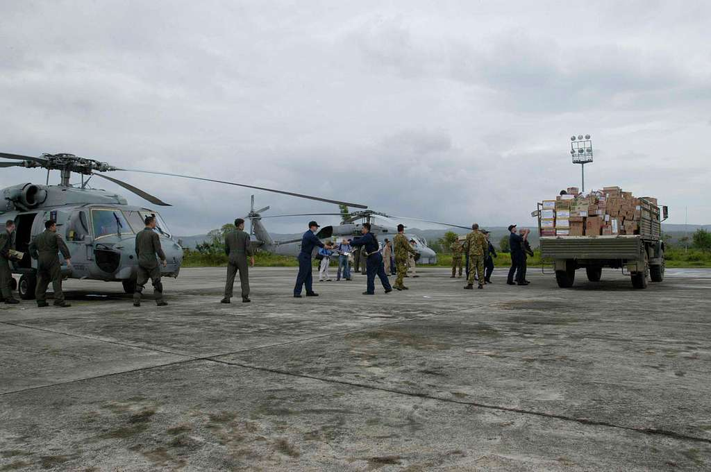 Sailors from USS Abraham Lincoln with the help of military members from Indonesia and Australia load United States Navy Seahawk helicopters with supplies to be distributed throughout the island.