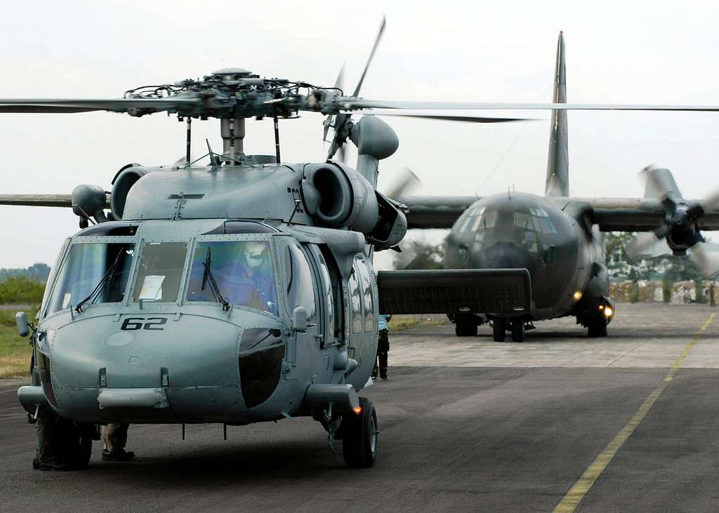 An MH-60S Knighthawk helicopter and an Australian C-130 Hercules cargo aircraft prepare for takeoff at the Sultan Iskandar Muda Air Force Base in Aceh, Sumatra, Indonesia.