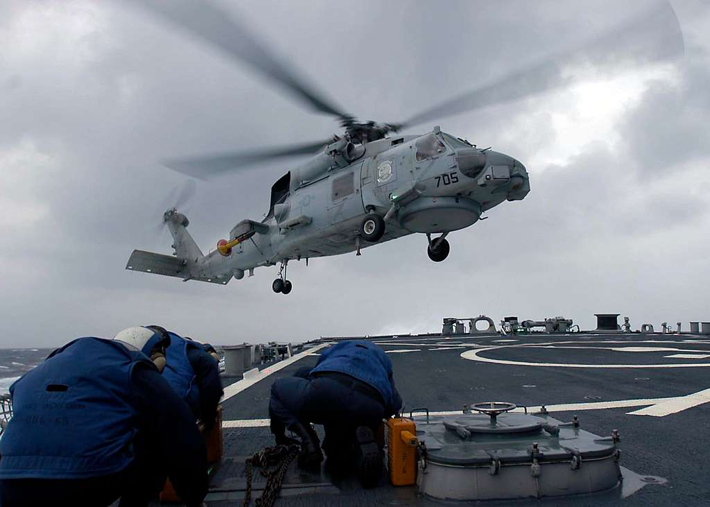 Sailors keep covered as an SH-60B Seahawk, assigned to the Saberhawks of Helicopter Anti-Submarine Squadron Light Four Seven (HSL-47), lands aboard the guided missile destroyer USS Benfold (DDG 65).
