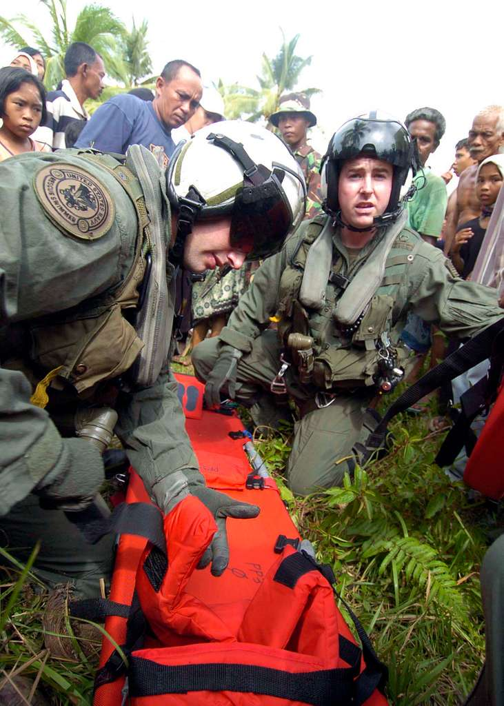 Two Naval air crewmen prepare a stretcher in a village near Aceh, Sumatra, Indonesia so that they can transport a seriously injured Indonesian woman to a medial facility.