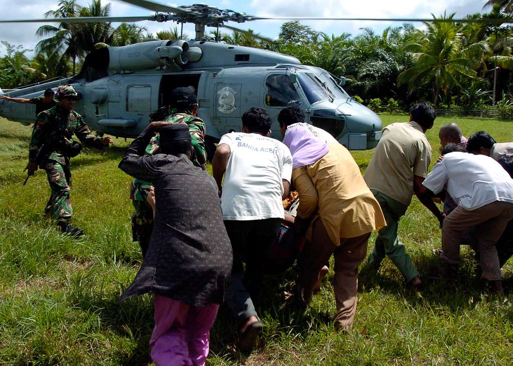 Indonesian civilians rush to load their injured into an SH-60B Seahawk helicopter.