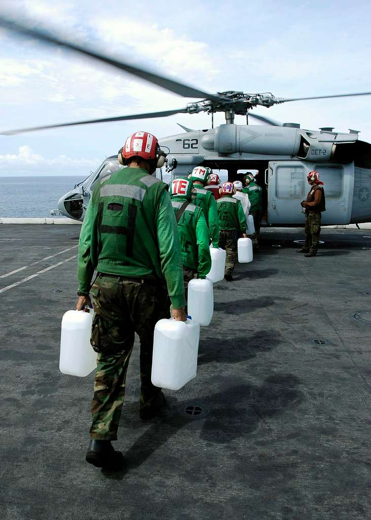 Sailor's aboard USS Abraham Lincoln (CVN 72) load jugs of purified water on board an awaiting MH-60S Knighthawk helicopter.