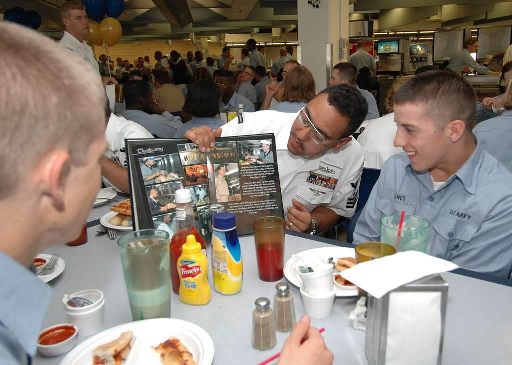 Chief Select Hull Technician Lucio Saraiva shows Seaman Recruits pages from the latest cruise book of USS John F. Kennedy (CV 67) during dinner on board Recruit Training Command Great Lakes.