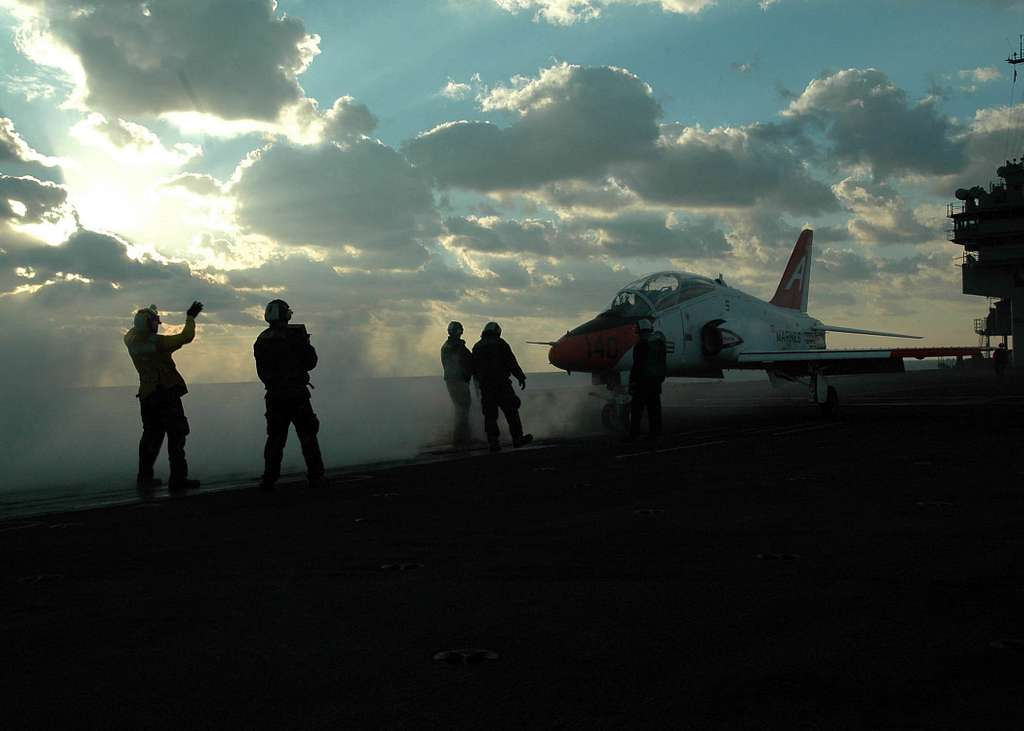 An Aviation Boatswains Mate directs a T-45 Goshawk onto a steam-powered catapult during flight operations aboard the conventionally powered aircraft carrier USS John F. Kennedy (CV 67).