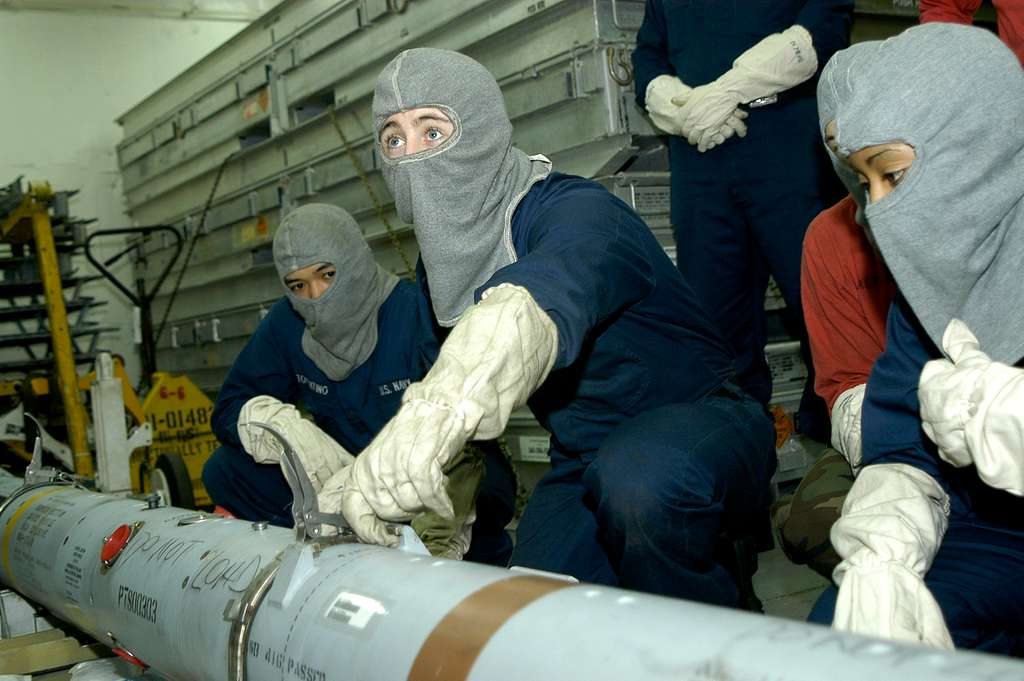 Airman Recruit Jacob Fritz, center, simulates steps to safely recover an air-to-air missile during a general quarters drill aboard the conventionally powered aircraft carrier USS Kitty Hawk (CV 63).