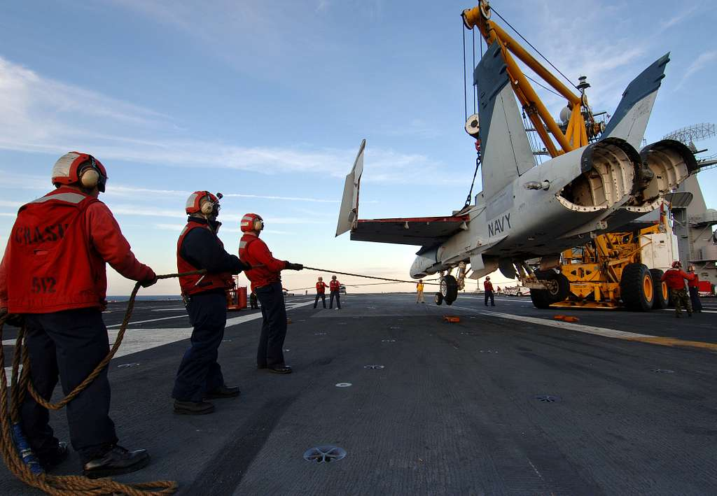 Crash and salvage personnel keep an F/A-18 Hornet training airframe steady as it is lifted from the landing area during a simulated crash landing training evolution aboard the Nimitz-class aircraft carrier USS Harry S. Truman (CVN 75).