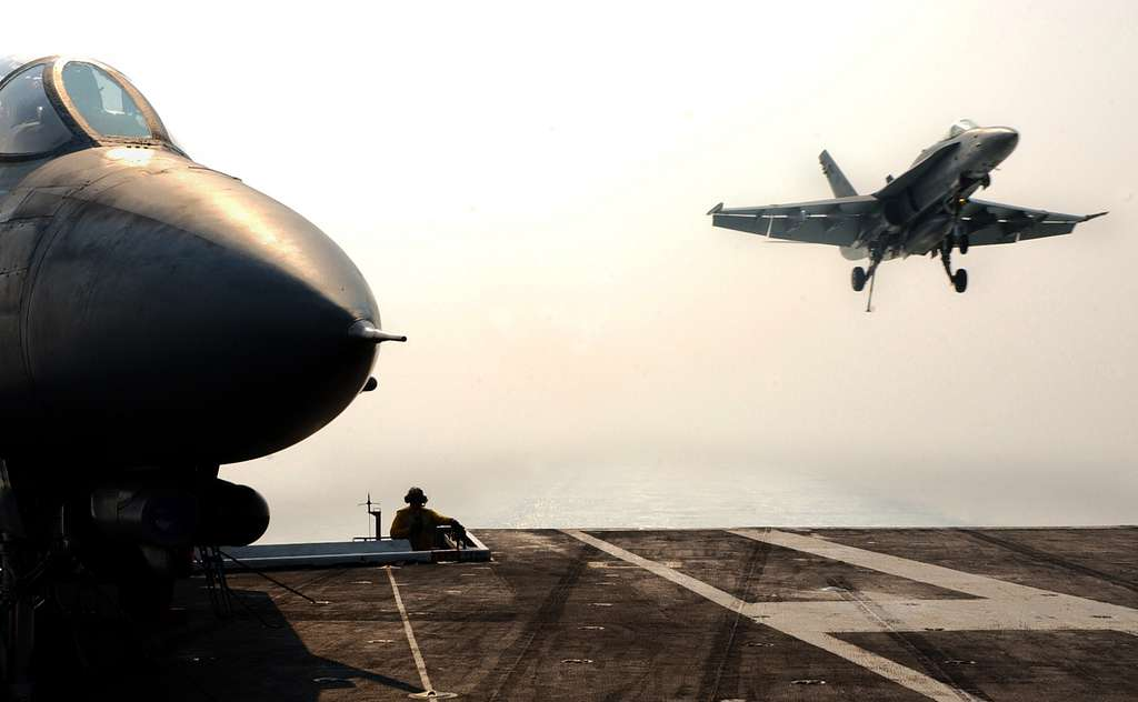 An F/A-18C Hornet prepares to make an arrested landing on the flight deck of the conventionally powered aircraft carrier USS Theodore Roosevelt (CVN 71).