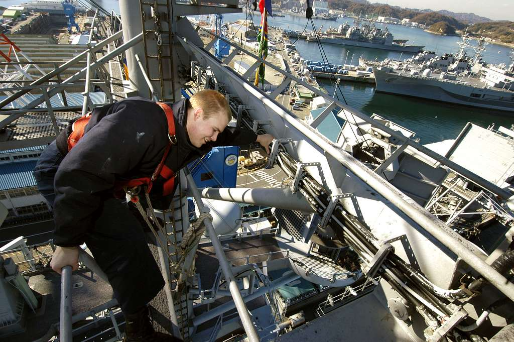 Quartermaster Seaman Matthew Lenerville, secures a safety line on railing while working aloft to hang holiday lights on the mast aboard the conventionally-powered aircraft carrier USS Kitty Hawk (CV 63).