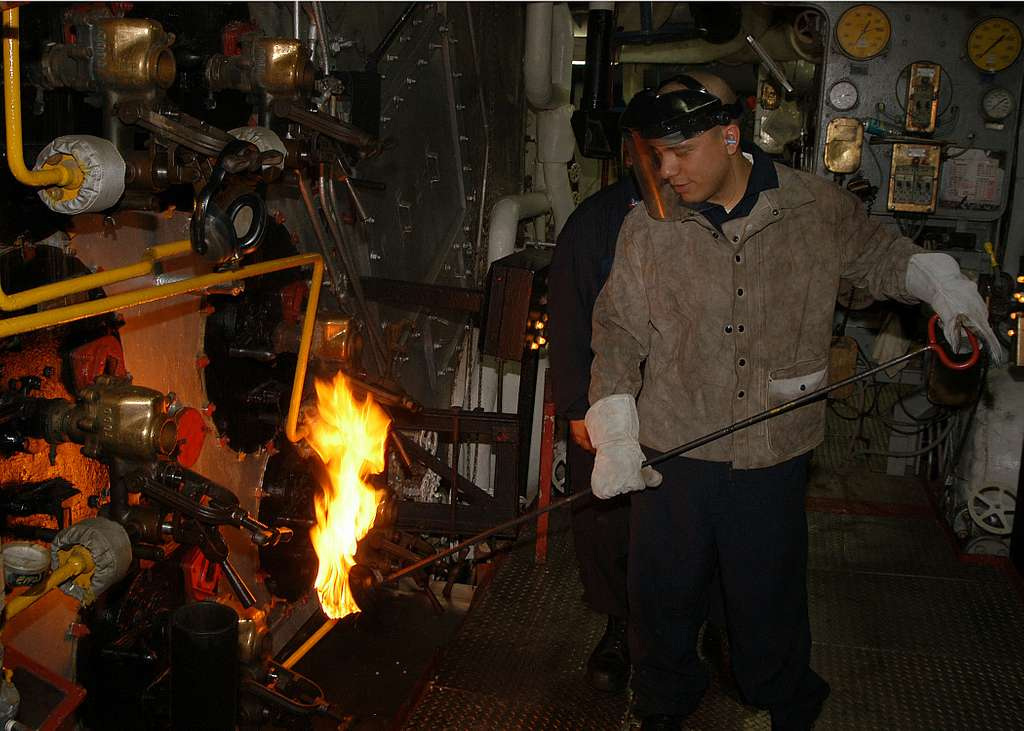 Fireman Roger Villatta ignites the torch that will be used to light fires in number three alpha boiler.