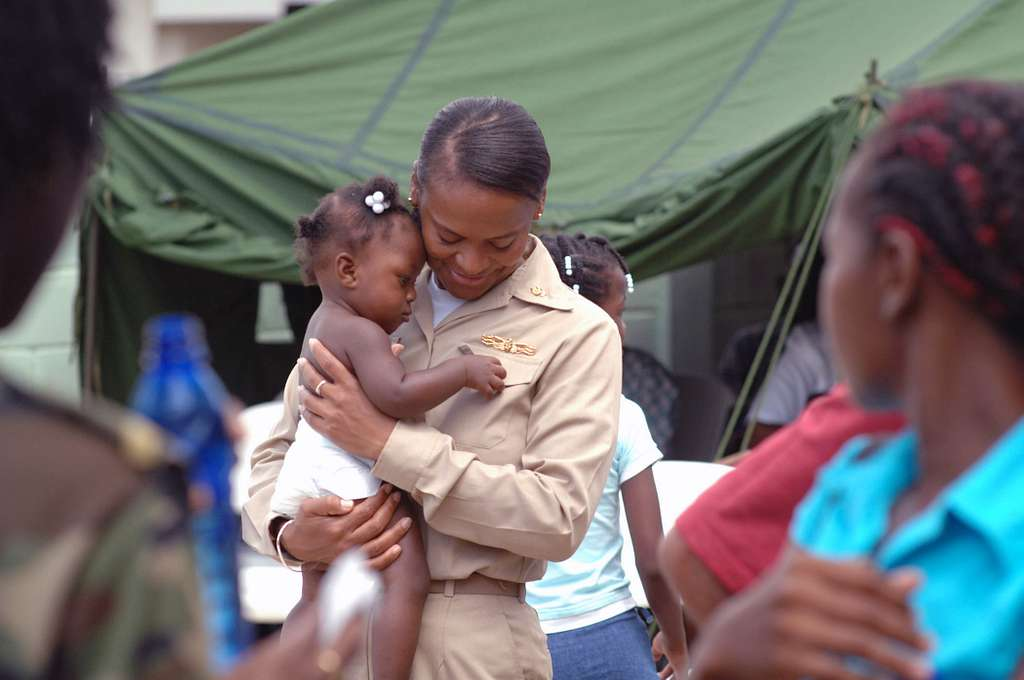 Lt. Cmdr. Andrea Petrovanie, attached to the Military Sealift Command hospital ship USNS Comfort (T-AH 20), calms a pediatric patient at Flustraat Clinic in Paramaribo, Suriname.