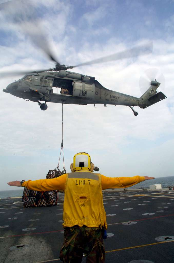 Aviation Boatswain's Mate (Handling) 3rd Class Gerson Gonzalez signals to an MH-60 helicopter during a vertical replenishment aboard the amphibious transport dock USS Cleveland (LPD 7).