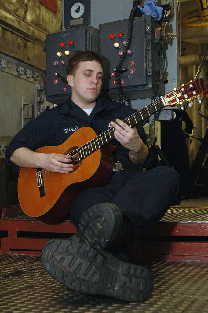 Machinist's Mate Fireman Apprentice Tommy Stanley, a native of Kirbyville, Texas, plays his guitar aboard the aircraft carrier USS Kitty Hawk (CV 63).
