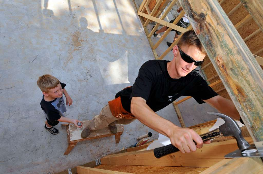 Center for Information Dominance (CID), Corry Station, nails hurricane straps at a Habitat for Humanity home in Pensacola while his son holds nails for him.