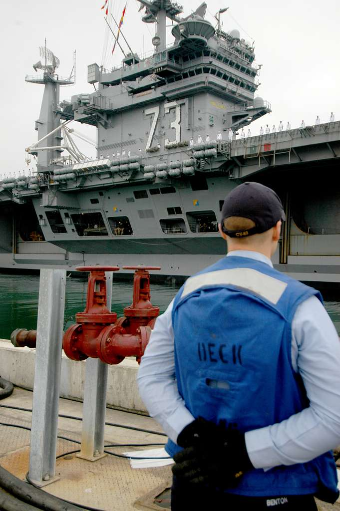 A Sailor assigned to the aircraft carrier USS Kitty Hawk (CV 63) stands at parade rest as the aircraft carrier USS George Washington (CVN 73) departs Naval Air Station North Island.
