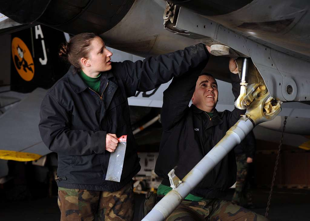 Aviation Structural Mechanic 2nd Class Jennifer McNutt and Aviation Structural Mechanic 2nd Class Jason Limbach inspect the tail hook assembly of an F/A-18 Hornet for corrosion.