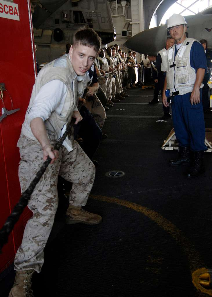 Sailors and Marines handle a messenger line used to pull a span wire from the Military Sealift Command fleet replenishment oiler Walter S. Deihl (T-AO 193) to the amphibious assault ship USS Boxer (LHD 4).