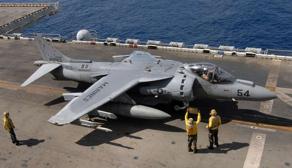 A pilot assigned to Marine Medium Helicopter Squadron (HMM) 163 receives signals from air handlers before take-off during AV-8B Harrier flight operations aboard the amphibious assault ship USS Boxer (LHD 4).