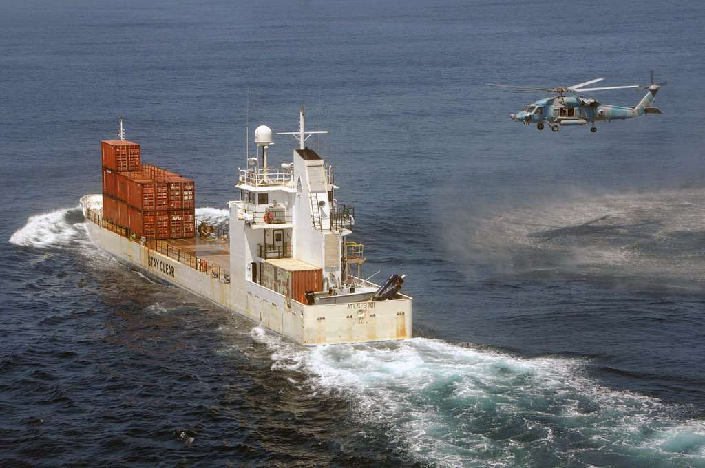 An HH-60H Seahawk, assigned to the Indians of Helicopter Anti-Submarine Squadron Six (HS-6), approaches a cargo ship to retrieve Explosive Ordnance Disposal (EOD) Technicians.