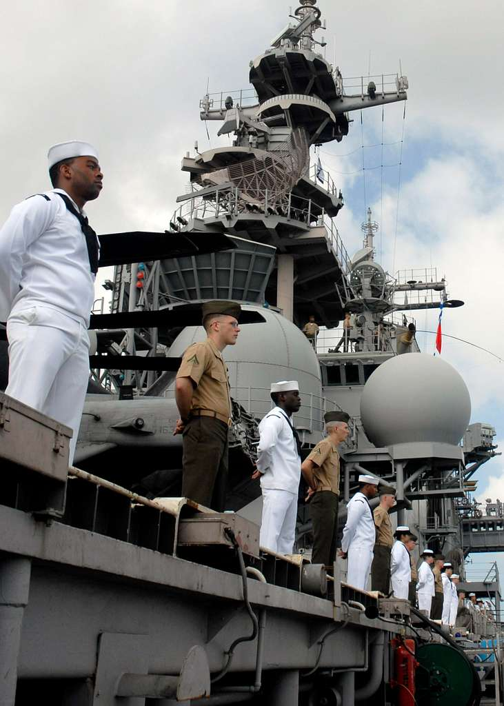 Sailors assigned to the amphibious assault ship USS Boxer (LHD 4) and Marines from the 13th Marine Expeditionary Unit (13th MEU) stand at parade rest while manning the rails as the ship departs Pearl Harbor.