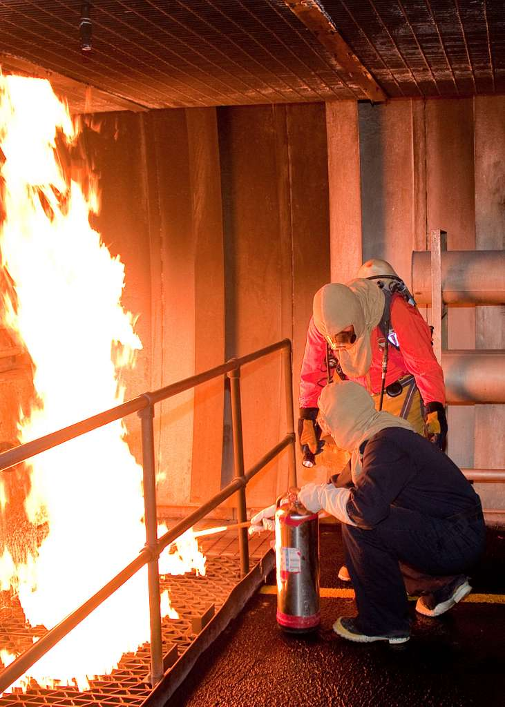 Senior Chief Machinist's Mate Paul Rose, from Vero Beach, Fla., instructs a damage control student in the Trident Training Facility fire trainer at Naval Submarine Base Kings Bay.
