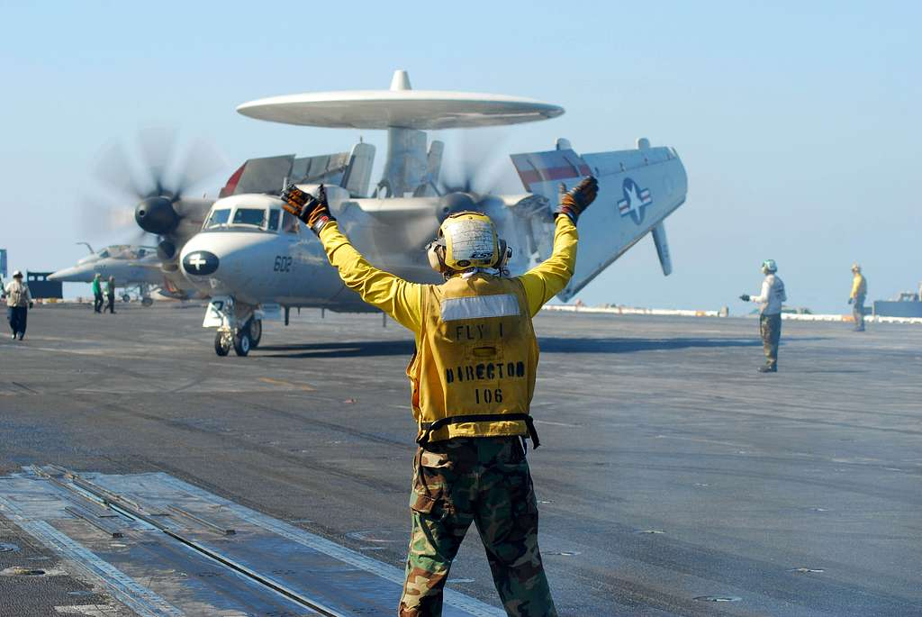 A flight deck director signals to an E2-C Hawkeye assigned to the Wallbangers of Carrier Airborne Early Warning Squadron (VAW) 117 during flight operations aboard the aircraft carrier USS Nimitz (CVN 68).