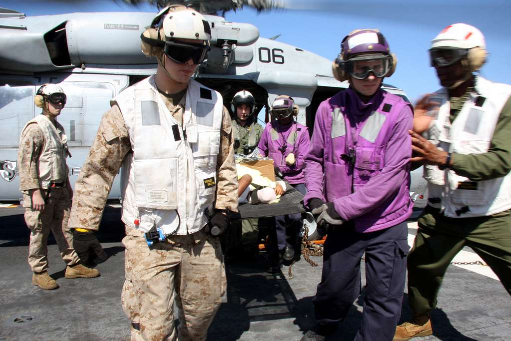 Marines and Sailors assigned to the 24th Marine Expeditionary Unit (24th MEU) and the Nassau Amphibious Ready Group carry a two-year-old Haitian child from an MH-60 Sea Hawk helicopter
