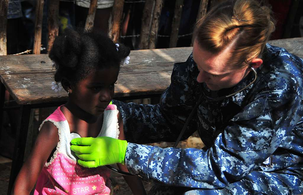 Hospital Corpsman 2nd Class Alexandra Howard, assigned to the guided-missile cruiser USS Bunker Hill (CG 52), performs a medical evaluation on a Haitian girl.