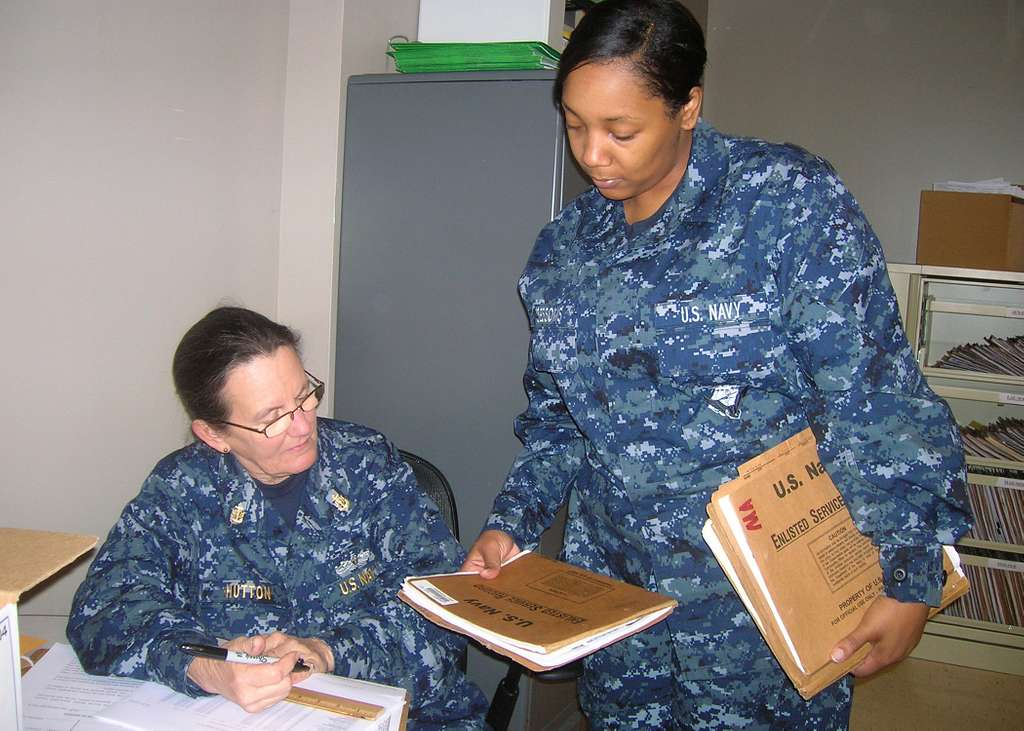 Chief Hull Technician Alicia L. Hutton, left, assigned to Reserve Unit USS Emory S. Land (AS-39), verifies field service records pulled for elimination.