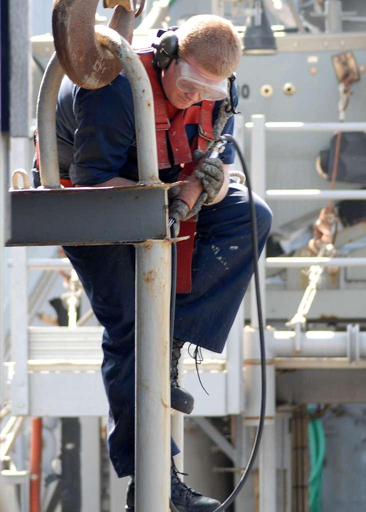 Sailor helps preserve USS Harpers Ferry.
