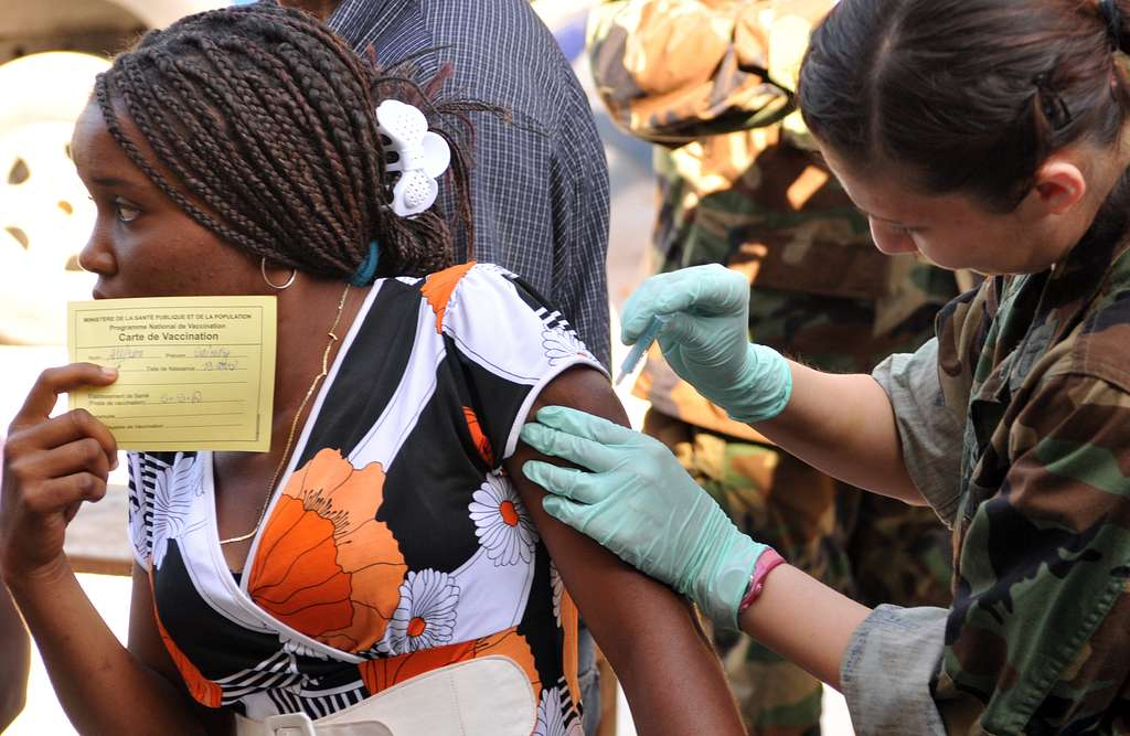 Hospital Corpsman 2nd Class Gina Martinez, a member of the U.S. Public Health Service, vaccinates a Haitian woman.