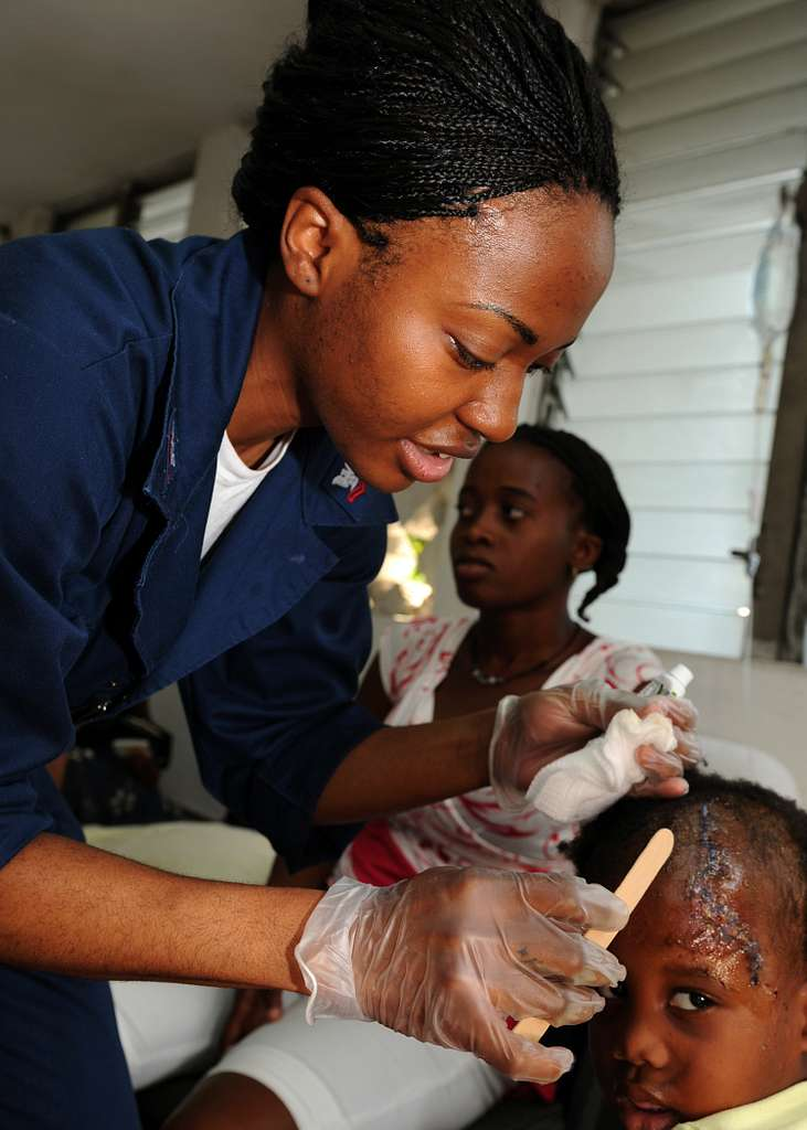 A corpsman applies an anti-bacterial ointment to the upper forehead of a Haitian child/