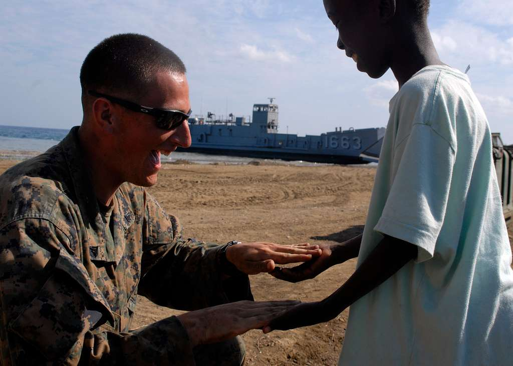 A Marine plays with a Haitian child.