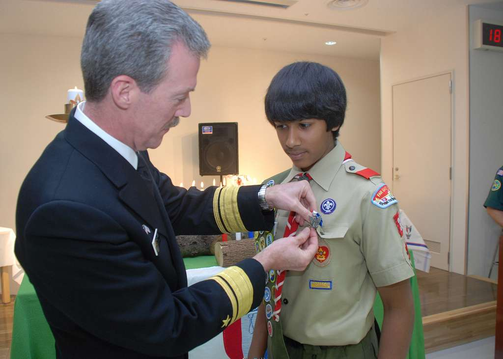 Rear Adm. Richard Wren, commander of U.S. Naval Forces Japan, pins an Eagle Scout badge on Nigal Shah, a member of the Far East Council, Boy Scouts of America Japan District, Troop 35.