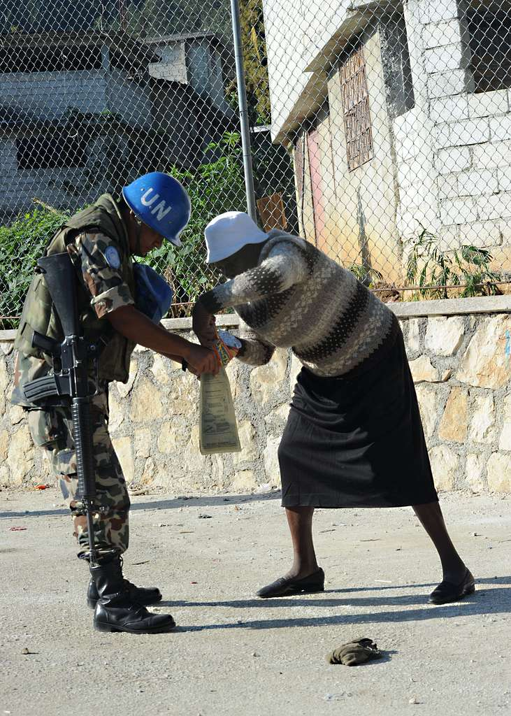 A U.N. peacekeeper from Nepal assists an elderly woman at a food distribution point in Kenscoff, Haiti.