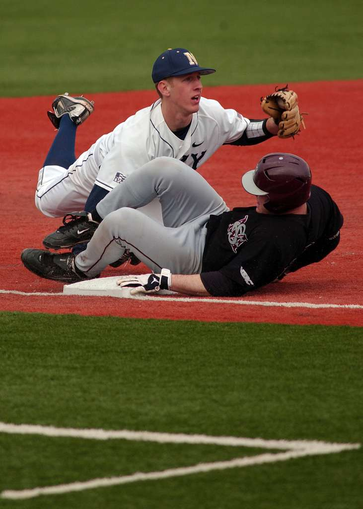 Midshipman 3rd Class Josh Moore dives to tag out a base runner during the U.S. Naval Academy home season opener at Max Bishop Stadium. Navy