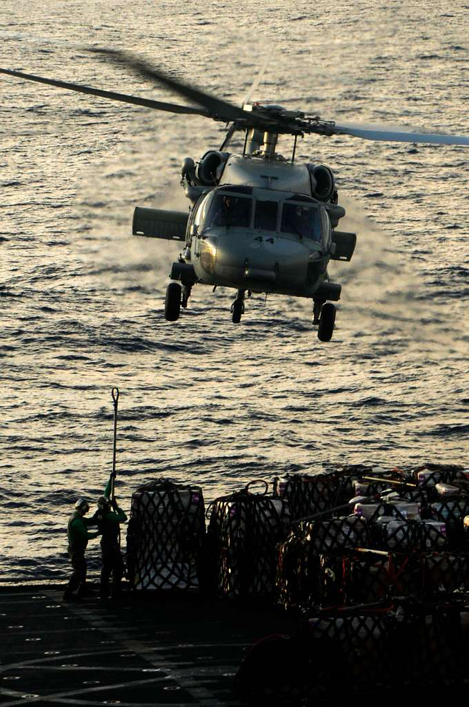 An MH-60S Sea Hawk helicopter assigned to the Wild Cards of Helicopter Sea Combat Squadron (HSC) 23 prepares to lift cargo.