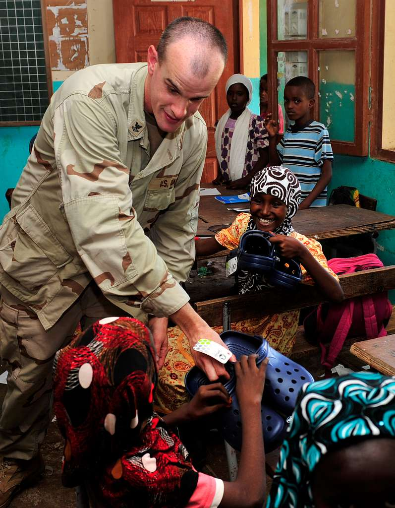 Religious Programs Specialist 2nd Class Norman R. Otters, from Oskaloosa, Iowa, hands out Croc shoes to students at the Guelleh Batal School in Djibouti.