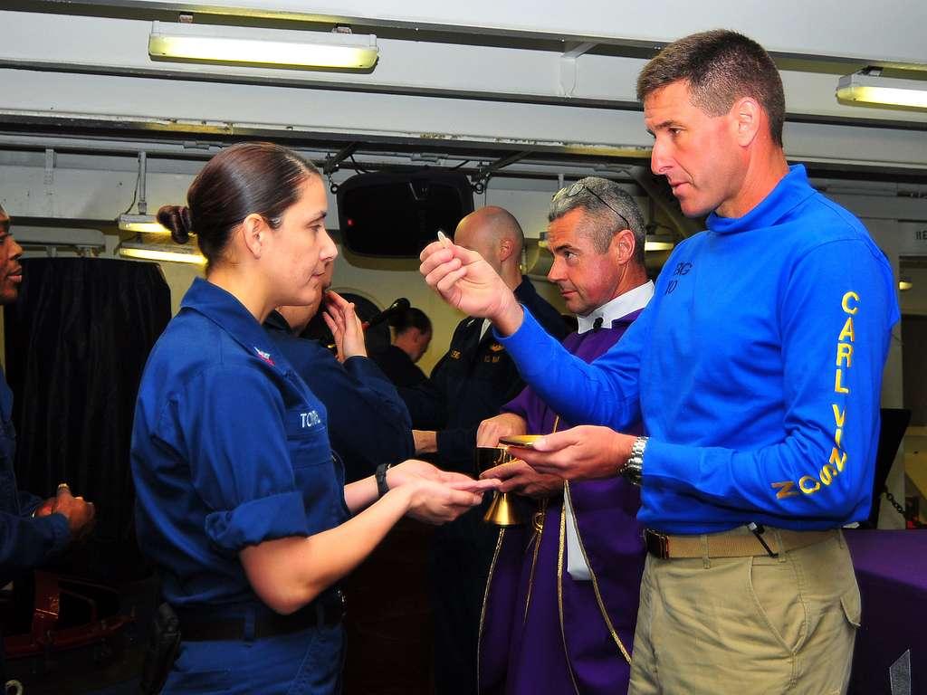 Cryptologic Technician (Maintenance) 1st Class Annette Torres receives communion from Cmdr. Putnam H. Browne.